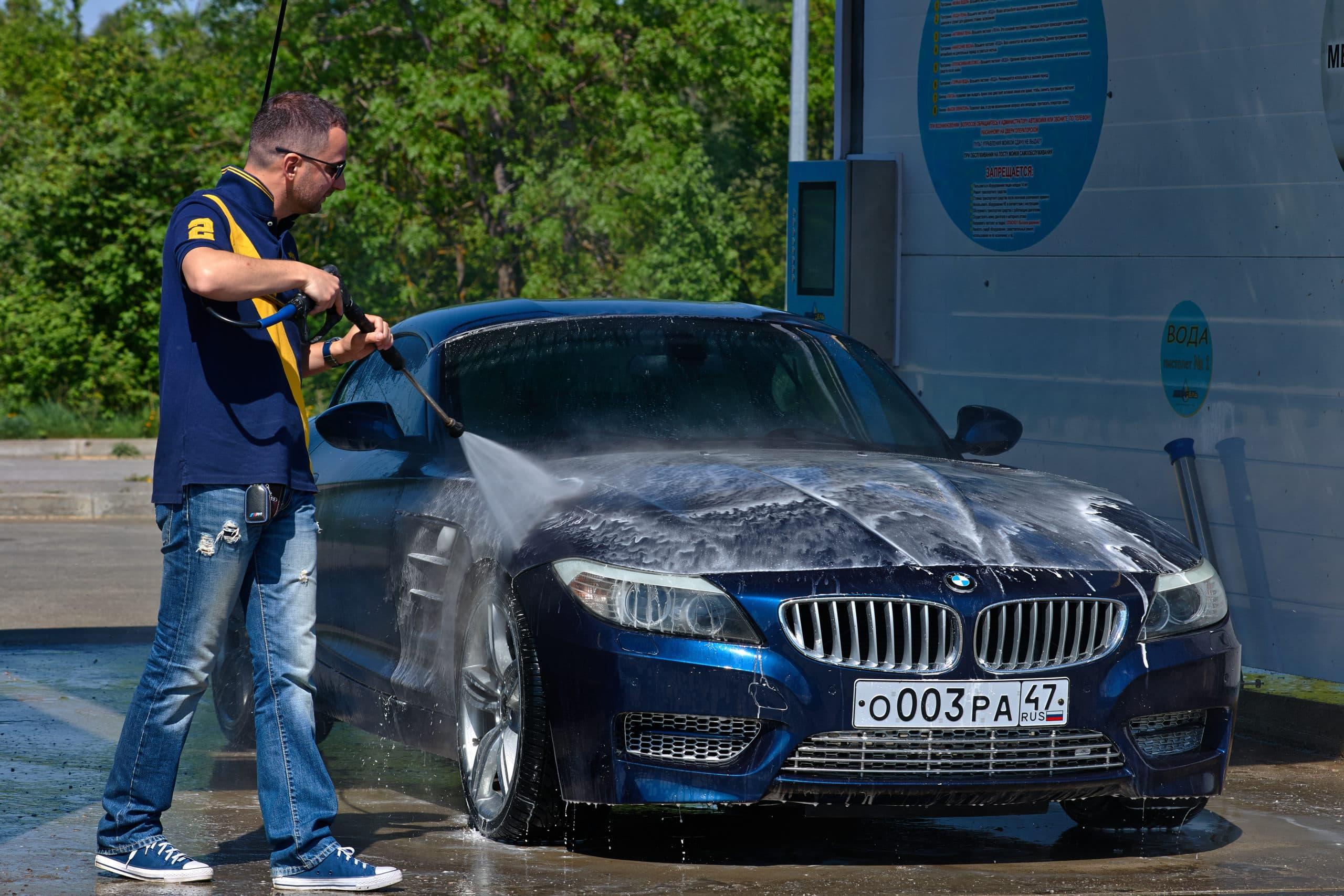 водитель моет автомобиль